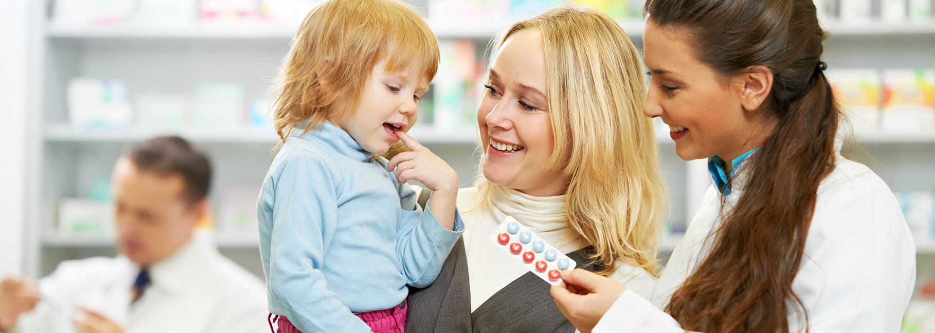 the woman is carrying her child while the pharmacist is handing the tablet